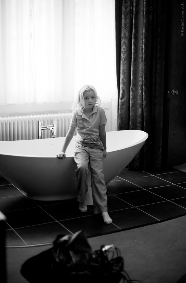 Flowergirl perches on the edge of a hotel bath