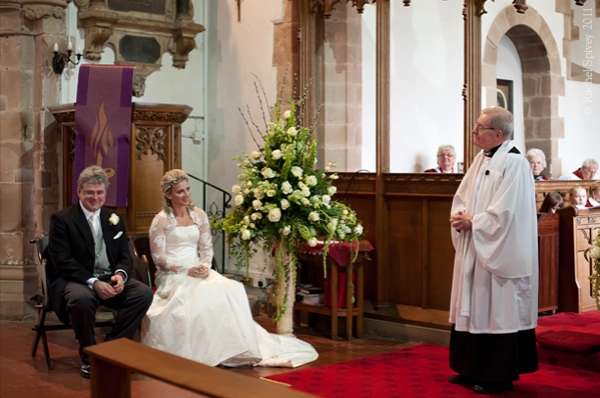 Bride and groom in the church with the vicar