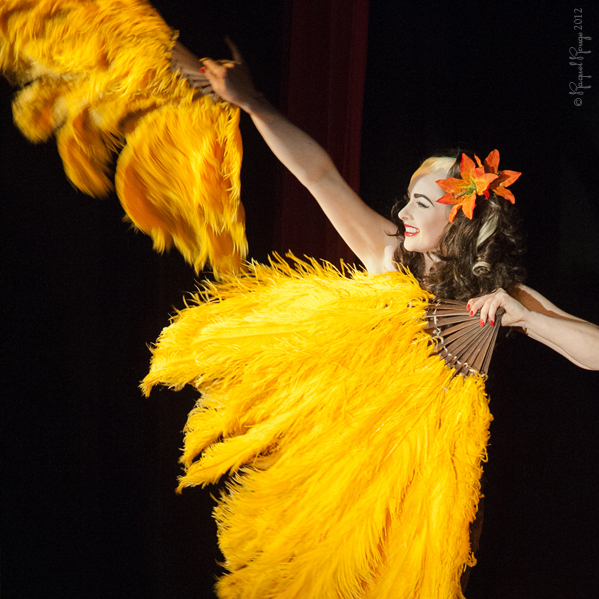 Missy Malone performs with yellow fans on stage