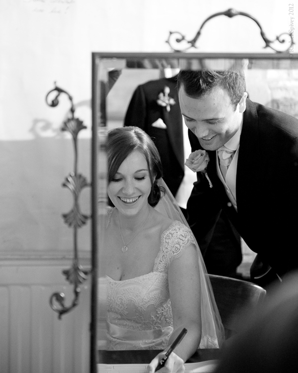 Reflection of Bride and Groom signing the register by Warwickshire Wedding Photographer Rachel Spivey