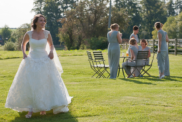 Candid shot of Bride crossing lawn with Bridesmaids in background