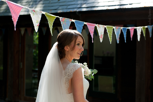 Happy Bride stood under coloured bunting