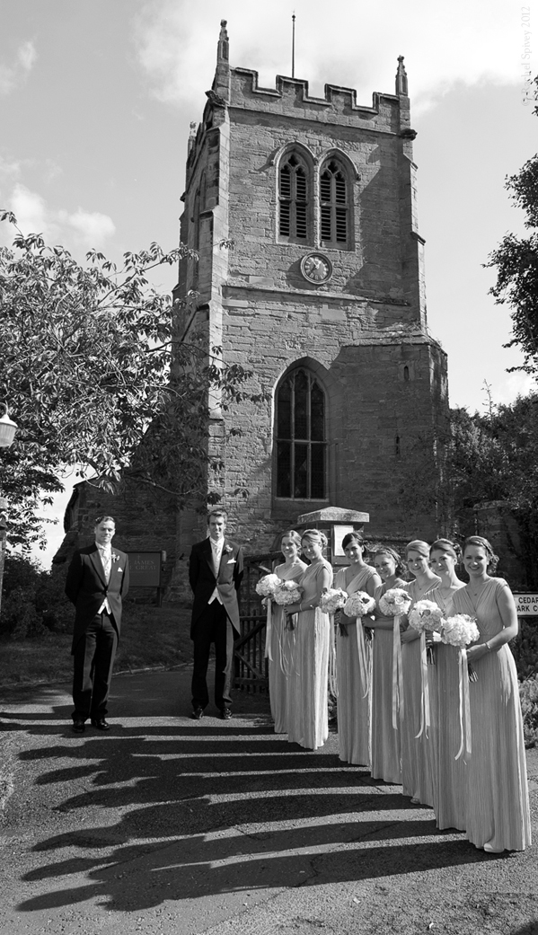 Six bridesmaids line up outside the church with Ushers in Warwickshire