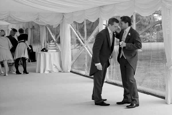 Groom and groomsman photographed in the marquee