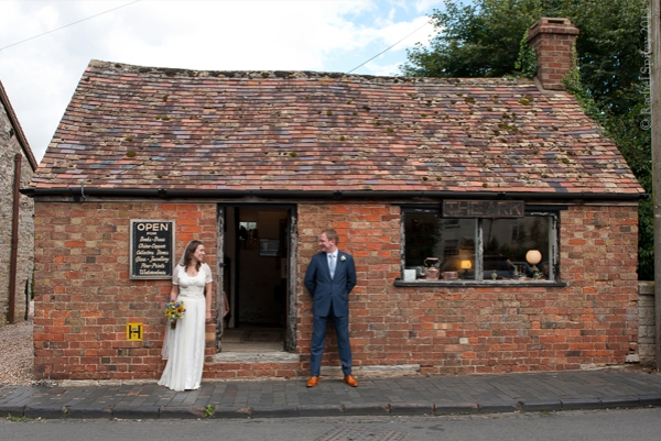 Wedding_couple_photographed infront_of_village_shop Gloucestershire