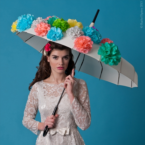 Bride holding a parasol decorated with flowers
