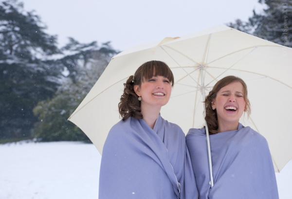 Bridesmaids in pashminas shelter from the snow