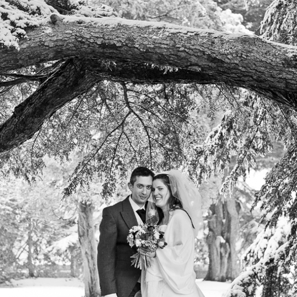 Bride and Groom photographed under a snowy tree